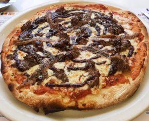 """PIZZA NAPOLITANA o PUTTANESCA o de ANCHOAS. NAPOLITANA Tomàquet, mozzarella, orenga, anxoves i olives Tomate, mozzarella, orégano, anchoas y aceitunas Tomate, mozzarella, origan, anchois et olives Tomato, mozzarella, oregano, anchovies and olives El término Puttanesca o Napolitana está más asociado a un plato típico de pasta, los espaguetis puttanesca, que a una pizza, aunque por los ingredientes que son, le pegan muy bien a una pizza. El origen de los espaguetis puttanesca, según el oráculo de la Wikipedia, está en Nápoles, y la historia detrás de esta maravillosa receta -cito textualmente- es esta: """"….que fuera costumbre de las prostitutas de Nápoles preparar este sencillo y rápido plato entre cliente y cliente. Se dice que una prostituta llamada Yvette la Francesa que tenía un local de comidas además de un burdel pudo haber inventado este plato…"""" En La Cirera hemos decidido transformar un plato de pasta en una exquisita pizza. Cómo preparar las anchoas en la pizza. Antes de nada, y para que quede como un checklist básico para esta receta y que marca la línea entre el éxito y el fracaso más rotundo, son las anchoas: Las anchoas tienen que ser cuanto más buenas mejor. Las anchoas hay que ponerlas al final, una vez las hayamos sacado del horno. Si metemos las anchoas en el horno, lo único que conseguimos es que se deshagan, y pierdan todo el sabor y la textura que tienen."""