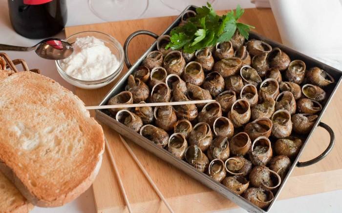 Los caracoles a la llauna se cocinan en lata de aluminio sobre brasas o al horno, con especies al gusto como pimentón, tomillo, romero, orégano, pimienta, perejil, ajo, mejorana, sal…