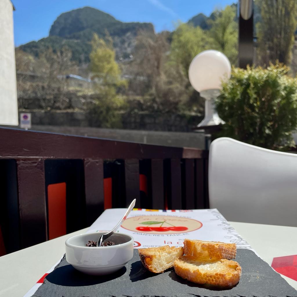 """El Restaurante La Cirera es un restaurante emblemático de la población de Encamp: uno de los mejores sitios para ir a comer o cenar de la población. Se encuentra situado junto al Telecabina Funicamp: es muy fácil de encontrar. Tiene zona propia de aparcamiento para clientes, 2 parkings cercanos y mucha zona azul en los alrededores. El Local: Se trata de una borda de grandes muros de piedra y vigas de madera en el techo, decorada al estilo típico de Andorra. Tiene capacidad para 150 personas y cuenta con 3 espacios totalmente diferenciados: una zona de barra y mesas con en la zona de la brasa, un salón comedor con capacidad para 100 personas y ventanales exteriores que ofrecen una magnífica vista panorámica de Encamp y una terraza muy soleada abierta todo el año (en invierno calentada con estufas y protegida con paravientos). Con zona de fumadores. Especialidades: El principal atractivo del restaurante es su magnífica brasa y su amplio horario. Especialidades en carnes, pescados y mariscos a la brasa, arroz con bogavante, pizzas y hamburguesas de Angus que se sirven desde el desayuno hasta la cena y tapas. Pizzas: las pizzas del Restaurante La Cirera son de las mejores de Andorra: masa fina, tamaño grande y elaboradas en horno de leña. Muy generosas en salsa e ingredientes. Servicio Para Llevar (Take-Away): El restaurante ofrece servicio """"Para Llevar"""" de todos los platos, pero especialmente de las pizzas. Son muy rápidos. Se puede llamar por teléfono para encargar (+376) 815 919 y luego pasar a recoger. No llevan a domicilio. Ambiente: Muy buen ambiente típico de Andorra. El restaurante es frecuentado tanto por turistas y esquiadores como por gente del país. Es un lugar ideal para desayunos, hacer el aperitivo, tapear, comer, cenar o tomar una copa a media tarde o por la noche. Tiene un amplio horario y siempre buen ambiente ;) Música en vivo: Actuaciones de música en vivo algunos días por la tarde y/o por la noche. Consultar por teléfono los días de actuación, ya qu"""